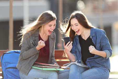 Excited students checking grades on smart phone sitting on a bench in a park Stock Photo