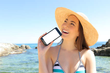 Happy tourist thinking showing smart phone blank screen on the beach on summer vacation