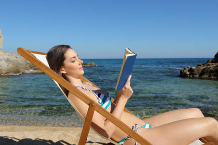 Side view portrait of a tourist reading a book on a hammock on the beach on summer vacation Stock Photo
