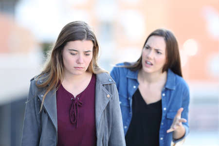 Angry girl scolding her stressed friend walking in the street Stock Photo