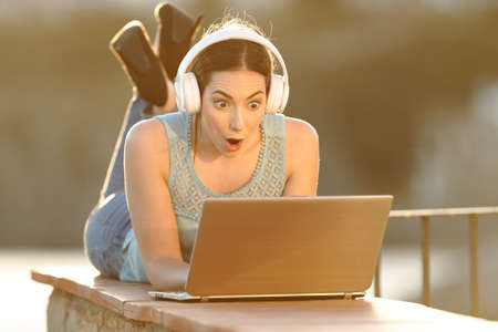 Surprised girl with headphones checking laptop lying on a balcony wall Stock Photo