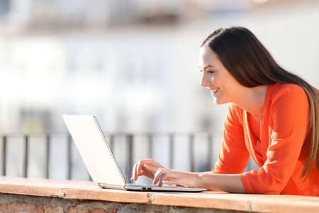 Side view portrait of a happy woman writing on laptop in a balcony