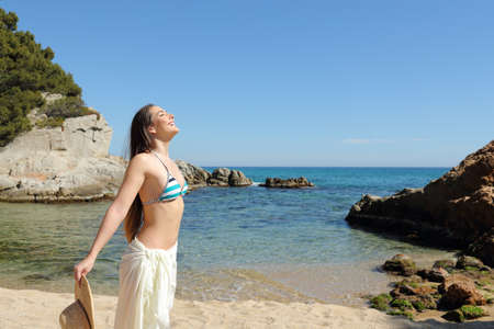 Side view portrait of a sunbather breathing deep fresh air on a beautiful beach on summer vacation