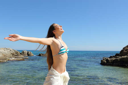 Happy tourist celebrating summer breathing fresh air on a beautiful beach on vacation