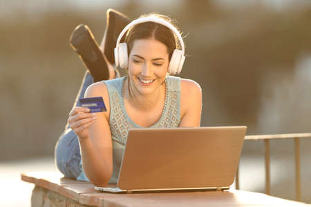 Happy woman uses credit card to buy online music or media with a laptop in a balcony wall Banque d'images - 120970846
