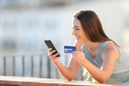 Happy girl is paying with credit card and smart phone in a balcony