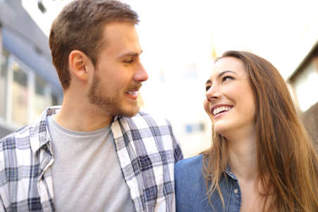 Happy couple walking talking looking each other falling in love in the street Stock Photo