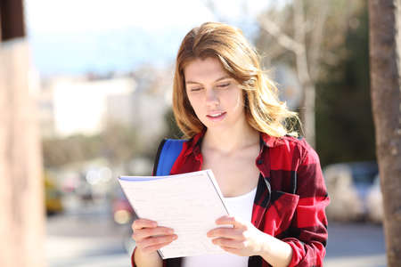 Front view portrait of a student studying walking in the street Banco de Imagens