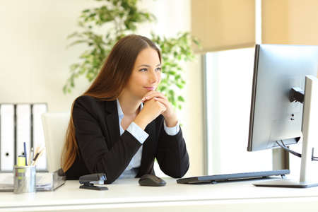 Satisfied office worker watching desktop computer content at workplace Stock Photo