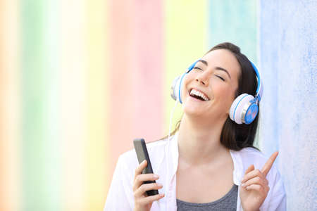 Happy girl singing listening to music with smart phone in a colorful street
