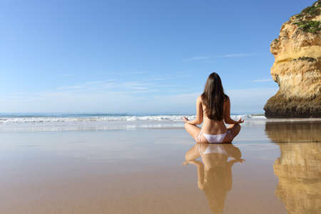 Back view portrait of a woman practicing yoga exercises on a solitary beach