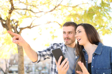 Happy couple talking and pointing away holding smart phone in a park