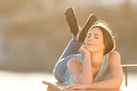 Relaxed woman breathing fresh air closing eyes lying on a balcony wall
