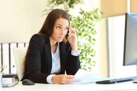 Verwirrte Geschäftsfrau, die am Telefon spricht und Computerinhalte ansieht, die versuchen, im Büro zu verstehen