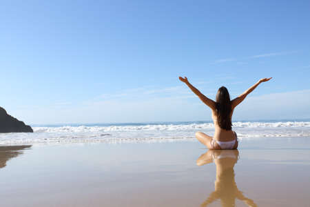 Back view full body portrait of a happy woman in bikini celebrating vacation on the beach Stock Photo