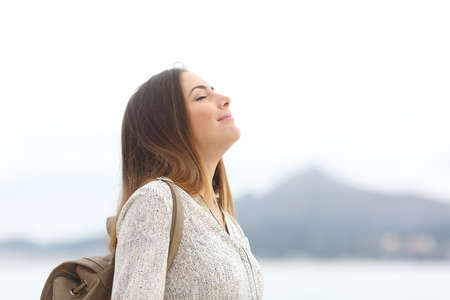 Side view portrait of a happy woman on the beach breathing fresh air Stock Photo