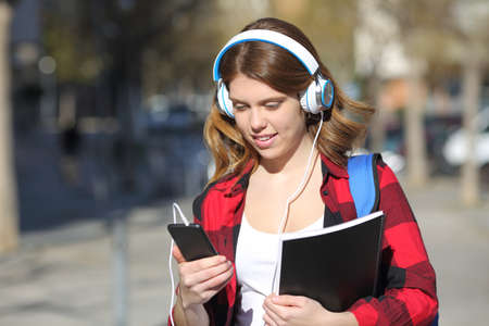 Student listens to music with headphones and smart phone walking in the street Stock Photo