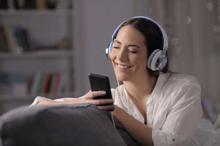 Happy woman listening to music feeling well sitting on a couch in the living room at home in the night Stock Photo