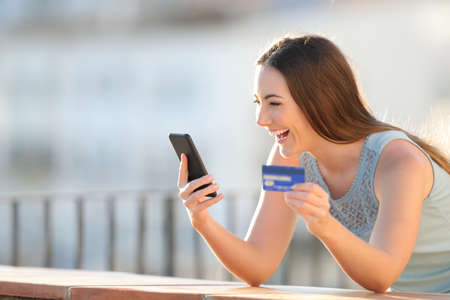 Excited girl is paying with credit card and smart phone in a balcony