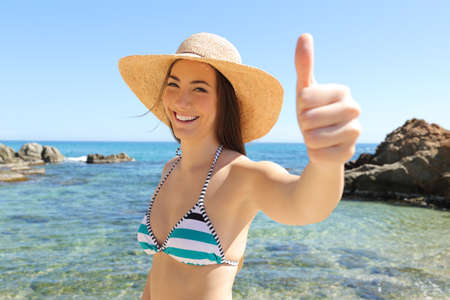 Happy tourist gesturing thumb up on a beautiful beach on summer vacation Stock Photo