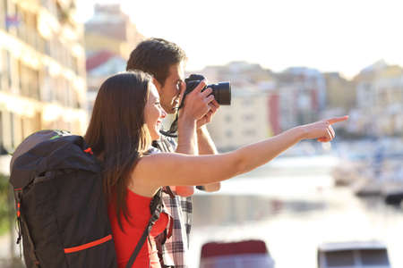 Two backpackers taking photos of landmarks on summer vacation