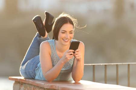 Full body portrait of a happy woman using a smart phone lying in a balcony
