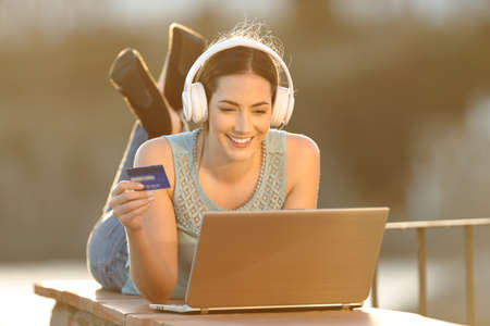 Happy woman uses a laptop to buy online music or media with credit card at sunset