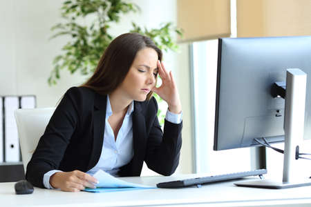 Worried office worker suffering headache and complaining at workplace