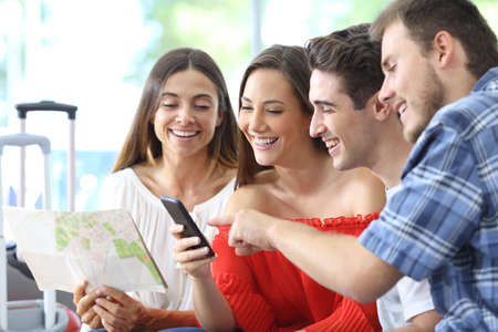 Group of tourists planning travel online on smart phone at home or hotel room Stock Photo