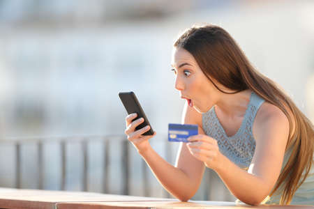 Amazed online buyer holding credit card and cell phone paying purchase in a balcony
