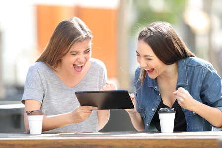 Two excited friends watching tablet online content sitting in a park Imagens
