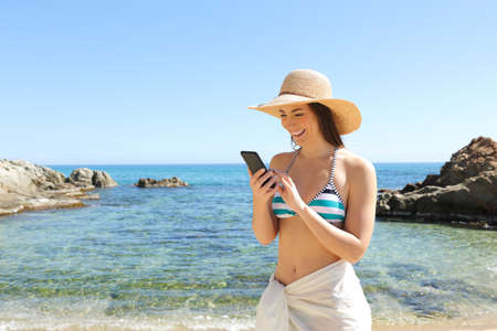 Happy tourist browsing smart phone on a beautiful beach on summer vacation