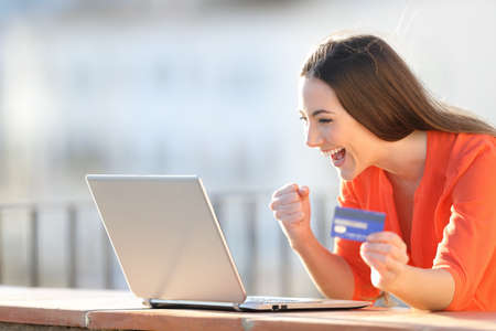Excited buyer holding credit card finding online offers on laptop in a balcony