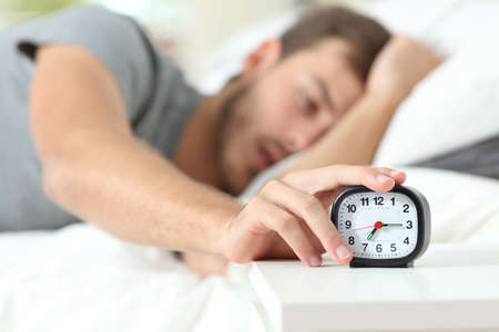 Tired man turning off alarm clock lying in the bed in the morning