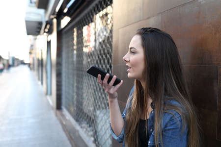 Side view portrait of a teen using voice recognition on smart phone in the street