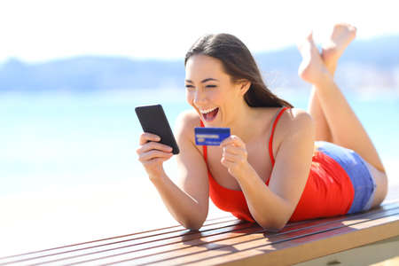 Excited girl finding ecommerce offers buying online with phone and credit card on the beach Фото со стока
