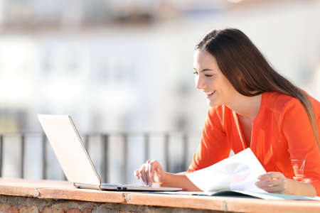 Happy entrepreneur working with laptop and charts in a balcony Banque d'images - 121189589
