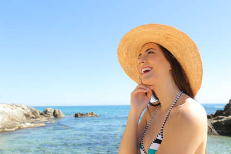Happy tourist dreaming looking at side on a beautiful beach on summer vacation Stock fotó