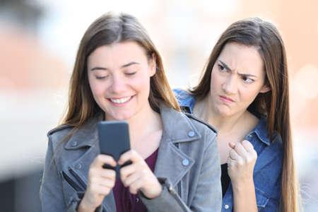 Retrato de vista frontal de una mujer enojada espiando a su amiga usando el teléfono en la calle Foto de archivo