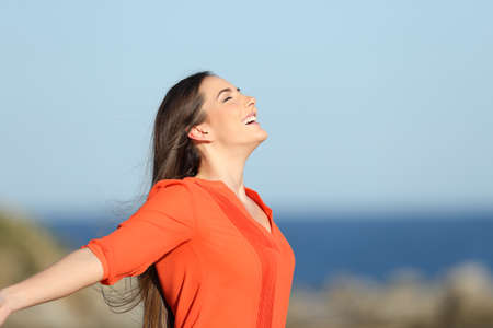Side view portrait of a happy woman breathing deep fresh air in the coast on summer vacation