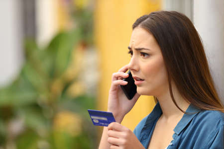 Worried online buyer talking on phone holding credit card in a colorful street Stock Photo