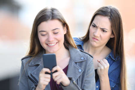 Angry girl spying the smart phone of a friend in the street Stock Photo