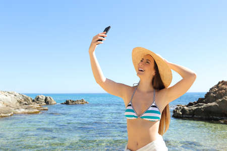 Happy tourist taking selfie with smart phone on the beach on summer holiday
