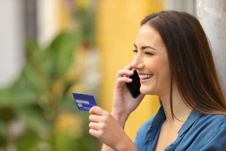 Happy woman talking on smart phone holding a credit card in a colorful street