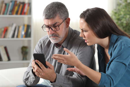 Confused father and daughter trying to use a smart phone sitting on a couch at home