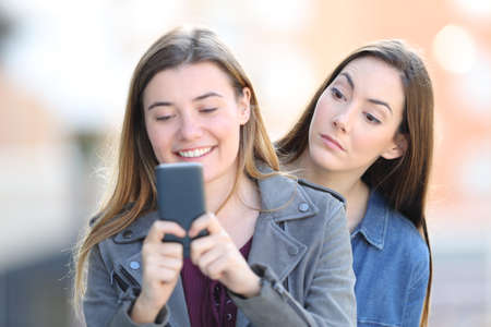 Gossip woman spying the smart phone of a friend in the street Stock Photo