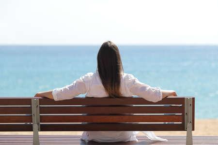 Vista posteriore ritratto di una donna felice che guarda il mare seduta su una panchina