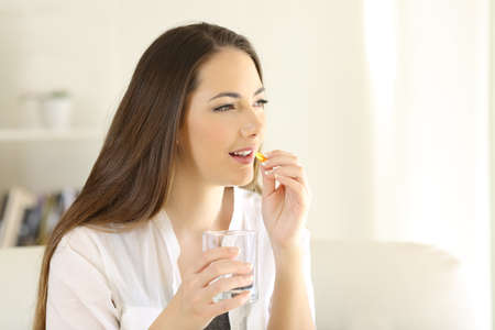 Happy woman taking vitamin pill holding glass sitting on a couch at home