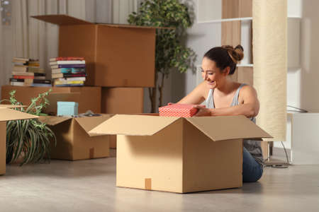 Happy woman moving home unboxing belongings sitting on the floor in the night