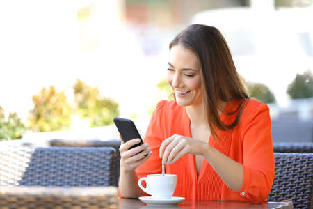 Happy woman using smart phone stirring coffee in a bar terrace
